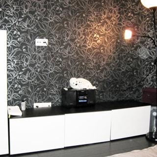 На фото: чистая комната со свежим ремонтом, светлая мебель, темные обои, полы - темный ламинат, у стены - низкий комод, на комоде - музикальный центр, слева - шкваф, справа - торшер.