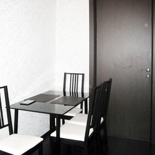 На фото: чистая комната со свежим ремонтом, качественная входная дверь, светлые обои, полы - темный ламинат, слева от двери у стены - стол, у стола - четыре мягких стула.