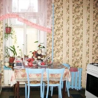 На фото: часть кухни, окно во двор, у окна - обеденный стол, справа от окна радиатор центрального отопления, еще правее у стены - газовая плита с духовкой, обои в цветочек, полы - линолеум.