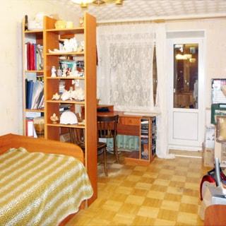На фото: чистая комната, светлая мебель, светлые обои, полы - светлый паркет, окно - стеклопакет и балконная дверь, у окна - письменный стол, слева у стены - диван и книжный шкаф