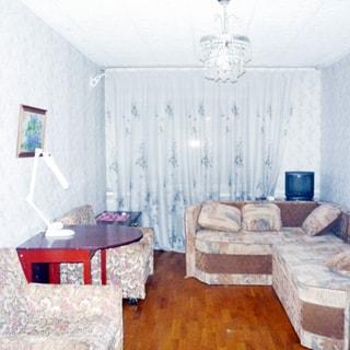 На фото: чистая комната в голубых тонах, мягкая мебель - два кресла слева и диван справа, слева у стены - стол, справа у окна - тумба с телевизором, светлые обои, полы - светлый паркет, на потолке - люстра