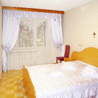 На фото: чистая светлая комната, окно - стеклопакет и балконная дверь, справа от окна у стены - двуспальная кровать, в изголовье кровати - тумбочка с настенным светильником над ней, светлые обои, полы - светлый паркет