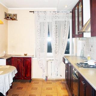 На фото: часть кухни, окно - стеклопакет, справа от окна вдоль правой стены - встроенная кухня: столы-тумбы, навесные шкафы, газовая панель, духовой шкаф, вытяжка, слева у стены - обеденный стол, стены: кухонный фартук - плитка, остальные - окрашены, полы - плитка