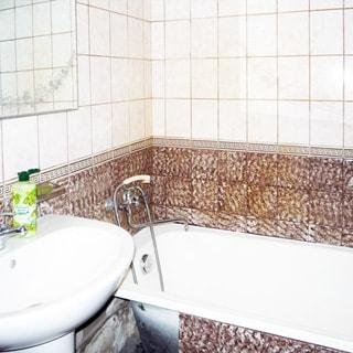 На фото: часть ванной комнаты, ванная со смесителем для ванной, керамическая раковина со смесителем, над раковиной - зеркало, стены - плитка в бежевых тонах