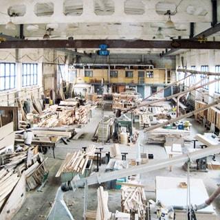 На фото: помещение столярного цеха с размещенным и работающим деревообрабатывающим оборудованием, кран-балка, готовая продукция, сырье