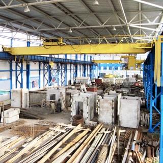 На фото: площадка хранения под крышей, два мостовых крана, железо-бетонные изделия, металлоконструкции, материалы, заготовки, сырье