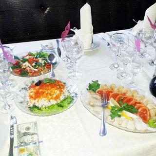 На фото: крупным планом участок сервированного стола, стеклянная посуда, бокалы, приборы, салаты и мясное ассорти