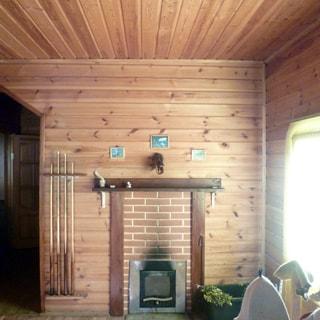 На фото: часть внутреннего помещения, печь, у печи - кадка с банными вениками, справа - окно, стены и потолок - обшиты деревом