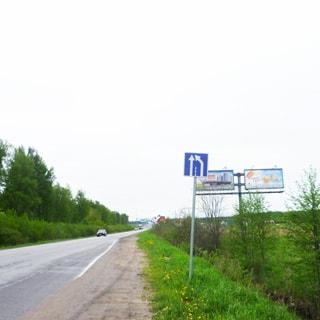 На фото: асфальтированная двухполосная дорога с отсыпаной обочиной, слева от дороги - кусты и лесополоса, справа от дороги - канава, кустарник и поля, вдоль дороги по правой обочине - дорожные знаки и рекламные щиты на высоких консолях
