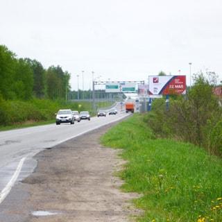На фото: асфальтированная двухполосная дорога с отсыпаной обочиной, справа от дороги - кусты и лесополоса, по дороге двигаются одиночные легковые и грузовые автомобили