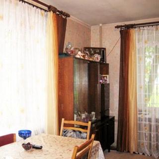 На фото: часть помещения жилой комнаты, комната - светлая, угловая, два окна, слева у окна - обеденный стол со стульями, между окнами в углу - сервант, под правым окном - батарея центрального отопления, на окнах - тюль и портьеры, стены оклеены обоями