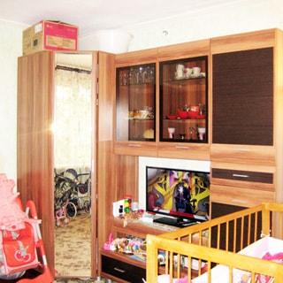 На фото: часть помещения жилой комнаты, угловой одежный шкаф с зеркальной дверью, справа от него - мебельная секция с отделениями для посуды и белья, местом под телевизор, еще правее - детская кроватка, слева от шкафа - детская коляска, в отражении зеркальной двери шкафа - окно