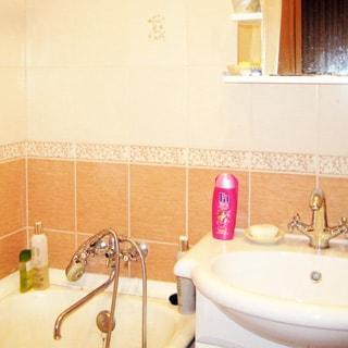 На фото: часть помещения ванной комнаты, керамическая раковина на стойке со смесителем, над ней полка и зеркало, слева от раковины - ванная со смесителем, стены облицованы керамической плиткой