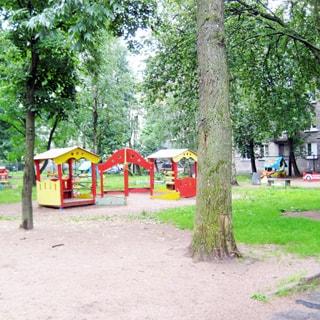 На фото: часть дворовой территории, благоустроенная оборудованная детская площадка, песочница, детские домики, газоны, песок, деревья