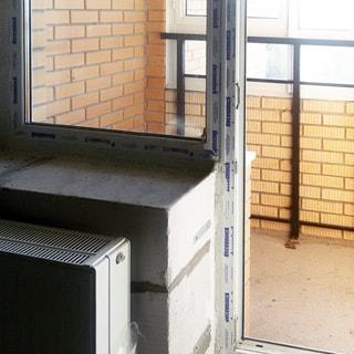 На фото: выход из комнаты на балкон, балконное окно и дверь - стеклопакет, , стены - под чистовую отделку, под окном - радиатор центрального отопления, дверь на балкон открыта. балкон - застеклен
