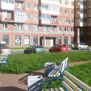 На фото: фасад дома со двора, по фасаду, начиная с тертьего этажа - балконы, одни застеклены, другие - открытые, в цокольном этаже - универсам, у дома - газон, тротуар, проезды и места для парковки автомобилей, во дворе - газон, пешеходные дорожки и садовые скамейки для отдыха
