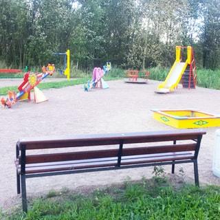 На фото: часть дворовой территории, оборудованная детская площадка, горка, качели, карусель, песочница, скамейка для родителей, вокруг площадки - газон, деревья