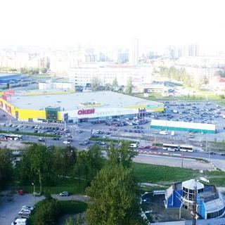 На фото: вид из окна, гипермаркет ОКей со своим открытым паркингом для автомобилей, проезжая часть с автомобилями и общественным транспортом, на дальнем плане торговый центр Континет и жилые кварталы