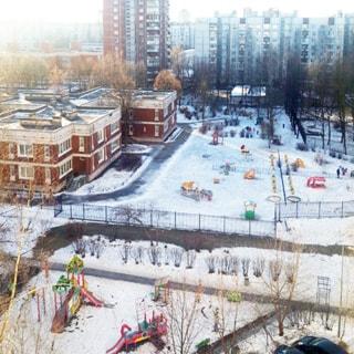 На фото: вид из окна во двор, во дворе - детский сад со своей огороженной территорией, перед ним - оборудованная детская площадка, рядом с ней правее - припаркованные автомобили, на территории высажены кусты и деревья