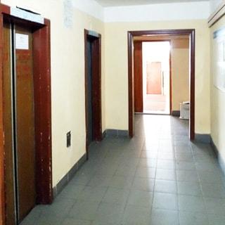 На фото: часть помещения лифтового холла первого этажа, два лифта, полы - плитка, стены окрашены, напротив лифтов на стене - доска объявлений, на дальнем плане - входной холл в парадную и металлическая входная дверь в подъезд