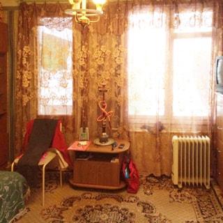 На фото: часть помещения жилой комнаты, одно окно, отдельно балконная дверь со стеклом, под окном батарея центрального отопления, между окном и балконной дверью у стены - журнальный столик, слева от стола - стул, справа от окна - комод, на комоде - телевизор, на полу - ковер, на потолке - люстра