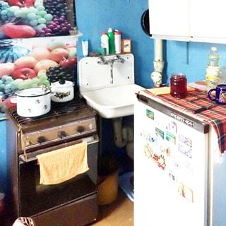 На фото: часть помещения кухни, прямо в углу - эмалированная мойка со смесителем, слева от мойки - четырехкомфорочная газовая плита с духовкой, справа у стены - холодильник, над ним - навесной кухонный шкаф, стены окрашены