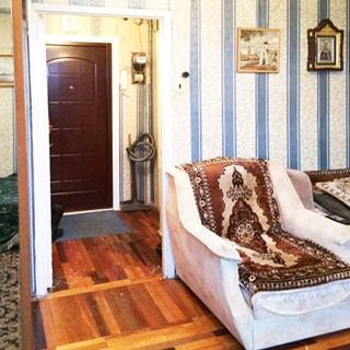 На фото: часть помещения жилой комнаты, дверь в прихожую открыта, справа от вдери - кресло, в прихожей видна входная металлическая дверь, справа от входной двери - электросчетчик, стены в комнате и в прихожей оклеены обоями, полы - паркет