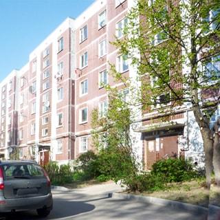 На фото: часть фасада пятиэтажного многоквартирного жилого дома 121 серии, фасад без балконов и лоджий, у дома высажены газоны, кусты, деревья, тротуар и проезды асфальтированы, припаркованы автомобили
