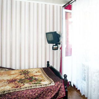 На фото: часть помещения жилой комнаты, справа окно с открытой балконной дверью, установлен стеклопакет, прямо у стены - кровать, слева от окна на кронштейне на стене подставка под телевизор с телевизором, кровать застелена покрывалом, стены оклеены обоями, полы - линолеум