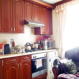 На фото: часть помещения кухни, справа - окно, слева от окна вдоль стены - кухонный гарнитур из встроенной стиральной машины, газовой плиты с духовым шкафом и тумб-столов с общей столешницей и навесных шкафов, фартук облицован керамической плиткой, над плитой - вытяжка, на столешнице - кухонная утварь и микроволновая печь, справа у окна - мягкое кресло