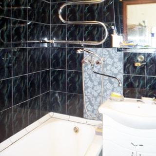 На фото: часть помещения ванной, слева у стены - эмалированная ванная, справа от нее - керамическая мойка на тумбе с дверцами, общий смеситель для манной и мойки, над мойкой - полка и зеркало, стены облицованы керамической плиткой