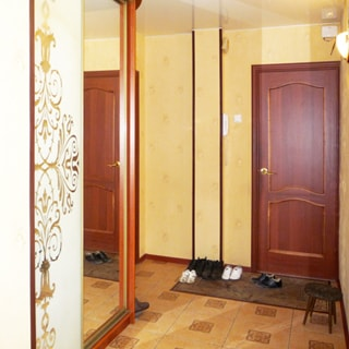 На фото: часть помещения прихожей, прямо входная дверь, слева от двери на стене - домофон, у левой стены - шкаф-купе с зеркальной дверью, стены оклеены обоями, полы - плитка, перед дверью коврик для обуви, справа у стены - табурет