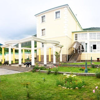 На фото: фасад загородного жилого дома, по фасаду - три этажа, справа к нему примыкает двухэтажный корпус с панорамным остеклением, в корпус ведет лестница под навесом, перед домом - колоннада, на земельном участке вымощенные дорожки, газоны, клумбы с цветами, уличное освещение