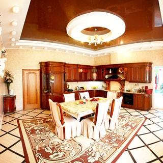 На фото: часть помещения кухни - столовой, на заднем плане угловой кухонный гарнитур, столы-тумбы и навесные кухонные шкафы, встроенная кухонная техника, плита и вытяжка, посредине комнаты ковер, на ковре - обеденный стол на шесть персон, вокруг стола - шесть мягких стульев, полы - паркет, стены - плитка, подвесные потолки, на потолке люстра и светильники