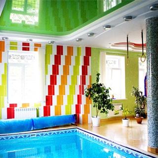 На фото: часть помещения для плавания и занятий спортом, слева на переднем плане чаша бассейна с водой, на заднем плане - стена с окнами, справа от бассейна - спортивная зона, на потолке - гимнастические кольца, полы и стены - плитка, на потолке - светильники