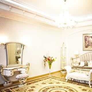На фото: часть помещения жилой комнаты - спальни, справа у стены - кровать с подголовником, перед кроватью - банкетка, слева от кровати у изголовья - прикроватная тумбочка со светильником на ней, слева у стены - дизайнерский туалетный столик с зеркалом и стулом без спинки перед ним, полы - паркет, на полу - ковер, стены оклеены обоями, на потолке - лепнина и люстра