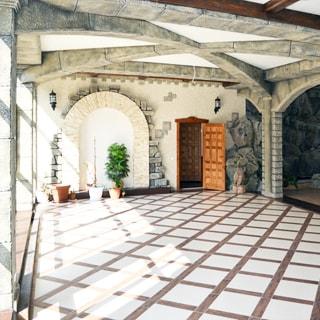 На фото: часть помещения просторного холла, слева падает свет от панорамных окон, помещение стилизовано под старинный замок, сводчатые каменные балки на потолке, колонны, арки, прямо на заднем плане - входная дверь, полы - плитка