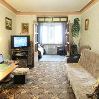 На фото: часть помещения жилой комнаты, прямо открытые двустворчатые двери в смежную комнату с большим окном, слева от двери в углу - тумба с телевизором, леввее у стены - компьютерный столик, справа от двери вдоль стены - мягкое кресло и диван, на полу - ковер, стены оклеены обоями