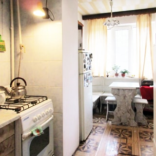 На фото: часть помещения кухни, прямо впереди - большое трехстворчатое окно, перед ним - мягкий уголок и обеденный столик с табуретами, слева у стены - двухкамерный холодильник, слева у стены на переднем плане - четырехкомфорочная газовая плита с духовкой, полы - линолеум, стены у плиты облицованы керамической плиткой