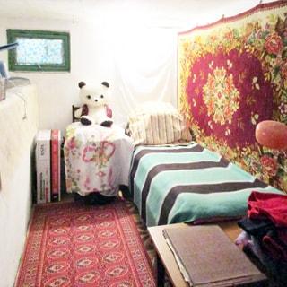 На фото: часть помещения жилой комнаты, прямо в стене - небольшое окно (форточка), справа у стены - односпальная кровать, на стене - ковер, справа у стены на переднем плане - обеденный стол, на полу - ковер