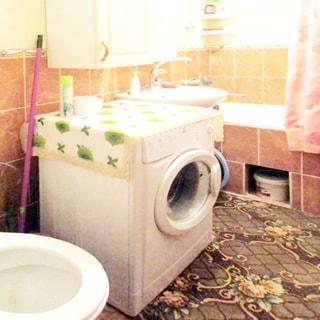 На фото: часть помещения совмещенного санузла, слева у стены - унитаз, правее - стиральная машина с фронтальной загрузкой, правее - керамическая раковина на стойке со своим смесителем, правее у стены - ванная со своим смесителем, над стиральной машиной на стене - шкафчик, над раковиной - зеркало с полкой, стены облицованы плиткой, на полу - ковролин