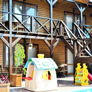 На фото: два этажа фасада дома, по фасаду на уровне второго этажа устроена галерея под кровлей с деревянным настилом, деревянными перилами и деревянной лестницей на второй этаж, опорные балки - из бруса, окна с балконными дверями, перед каждым окном - столик со стульями, стены облицованы блок-хаусом, перед домом детская площадка, дерево в кадке, территория вымощена тротуарным камнем