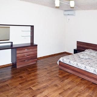 На фото: часть помещения жилой комнаты-спальни, справа у стены - двуспальная кровать с деревянным подголовником и прикроватной тумбочкой, слева у стены - туалетный столик с зеркалом, полочками и тумбой с ящиками, прямо в углу под потолком - кондиционер, стены окрашены, полы - ламинат, потолок - вагонка, на потолке - люстра