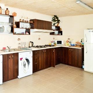 На фото: часть помещения кухни, встроенный кухонный гарнитур, столы-тумбы, навесные шкафы и полки, сушилки для посуды, справа у стены - двухкамерный холодильник, прямо в углу на столешнице - микроволновая печь, левее - две четырехкомфорочные газовые варочные поверхности, над ними - вытяжка, левее - стиральная машина с фронтальной загрузкой, левее - металлическая мойка со смесителем, стены - окрашены, полы - плитка, потолок - вагонка, на потолке - светильник