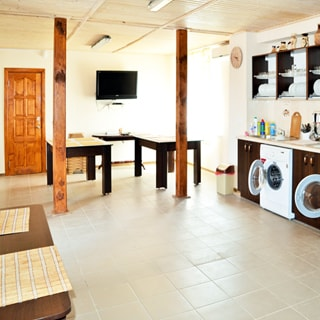 На фото: часть помещения столовой, справа вдоль стены - кухонный гарнитур из тумб-столов с общей столешницей, навесных полок и шкафов, встроенная стиральная машина с фронтальной загрузкой, слева у стены - обеденный стол, прямо у дальней стены два обеденных стола, слева от них - входная дверь, на стене - телевизионная панель, справа - окно, справа от окна под потолком - кондиционер, стены окрашены, полы - плитка, потолок - вагонка, на потолке - светильники