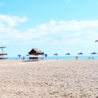 На фото: часть территории песчаного пляжа, зонтики от солнца, душевые кабинки, песок, море и голубое небо с легкими облачками