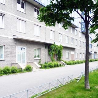 На фото: часть фасада смногоэтажного многоквартирного жилого жилого дома, первые три этажа облицованы декоративным камнем, окна - стеклопакеты, застекленные лоджии по фасаду - с четвертого этажа, на первом этаже коммерческие помещения с отдельными входами с крыльцом и ступеньками, перед домом - огороженный газон и широкий тротуар, между тротуаром и проезжей частью - широкий газон, высажены деревья