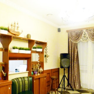 На фото: часть помещения зала, одно окно со шторами, вдоль левой стены - тумбы со стеллажами, на полках стеллажа - декоративные растения и интерьерные украшения, прямо в углу - штатив со звуковой колонкой, стены - окрашены, на полу - плитка, на потолке - элементы вентиляции и люстра