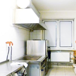 На фото: часть помещения кухни, одно окно, установлены стеклопакеты, под окном - радиатор центрального отопления, полы и стены в пол-высоты облицованы плиткой, слева у стены - разделочные столы с металлической столешницей, жарочная плита с духовым шкафом, над плитой - вытяжка