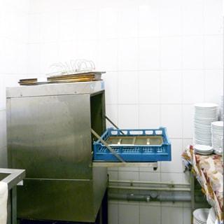 На фото: часть помещения для мойки посуды, стены в пол-высоты облицованы плиткой, прямо в углу - посудомоечная машина, справа у стены стол и стеллаж для чистой посуды